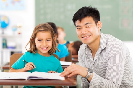 Foto de caring elementary school teacher helping student in classroom - Imagen libre de derechos