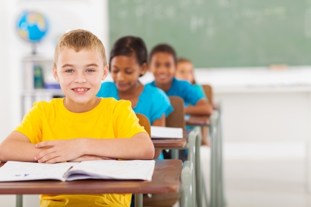 Photo for cute elementary schoolboy with classmates in classroom - Royalty Free Image