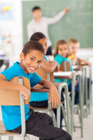 Photo pour smiling elementary school boy in classroom looking back - image libre de droit