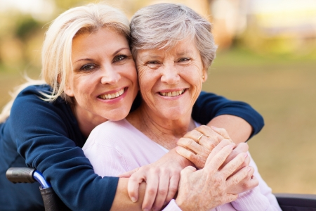Photo for cheerful middle aged woman embracing disabled senior mother outdoors - Royalty Free Image