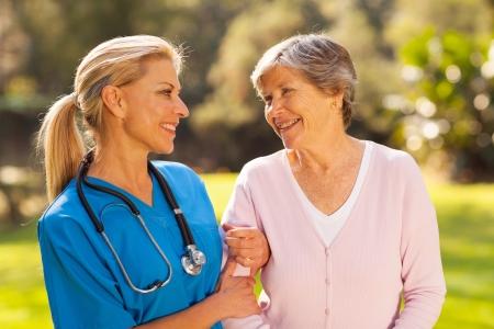 Photo pour caring nurse talking to senior woman outdoors - image libre de droit