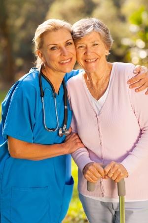 Foto de friendly mid age caregiver hugging senior patient outdoors - Imagen libre de derechos