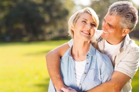 Photo pour cute middle aged couple embracing outdoors  - image libre de droit