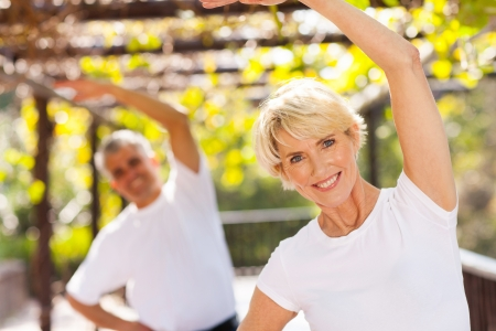 Foto de active senior woman exercising with husband outdoors - Imagen libre de derechos