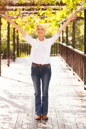Photo pour happy mid age woman with arms outstretched outdoors - image libre de droit