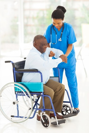 Foto de friendly african caregiver helping senior man getting up from wheelchair - Imagen libre de derechos
