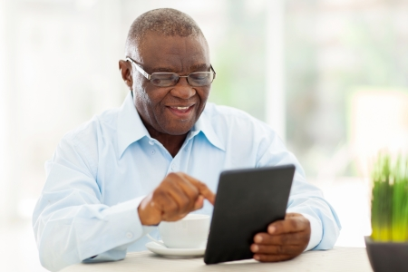 Photo pour cheerful senior african american man using tablet computer at home - image libre de droit