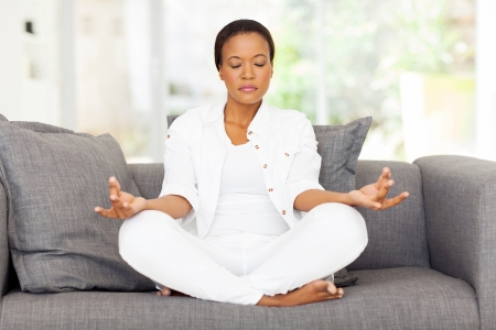 Photo pour beautiful young african woman meditating at home - image libre de droit