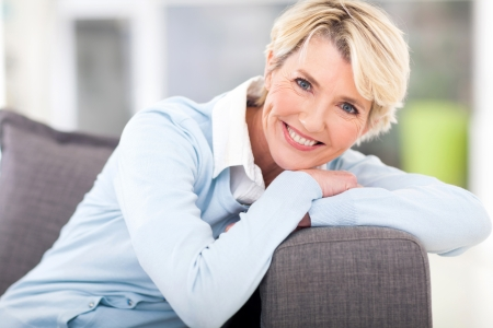 Foto per pretty senior woman relaxing on a couch at home - Immagine Royalty Free