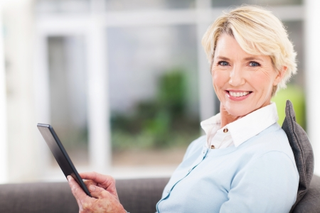 Foto per elegant middle aged woman using tablet pc at home - Immagine Royalty Free