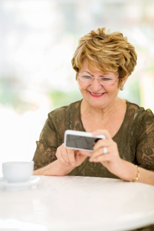 Photo for happy elderly woman reading emails on smart phone at home - Royalty Free Image