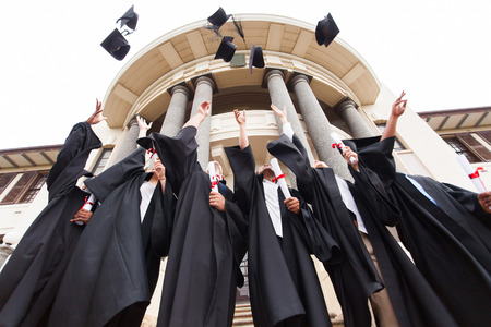 Photo for group of happy graduates throwing graduation hats in the air celebrating - Royalty Free Image