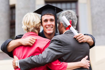 handsome young male graduate hugging his parents at graduation