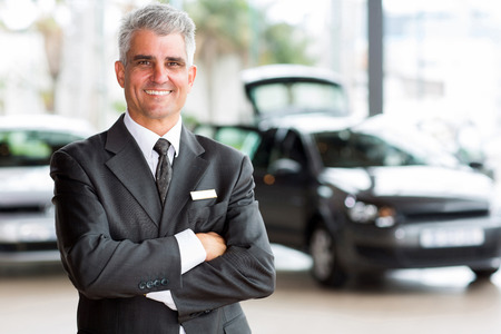 Photo pour confident senior car dealer principal standing in showroom - image libre de droit