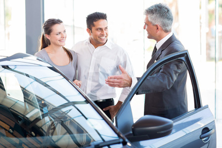 Photo pour mature salesman showing new car to a couple in showroom - image libre de droit