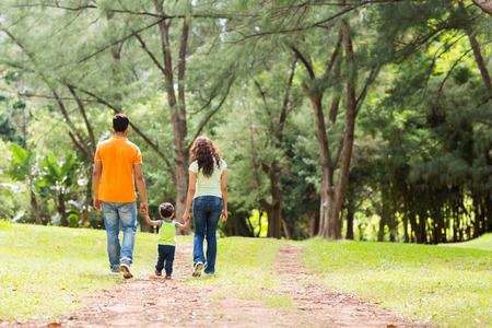 Foto de rear view of young family holding hands walking in forest - Imagen libre de derechos