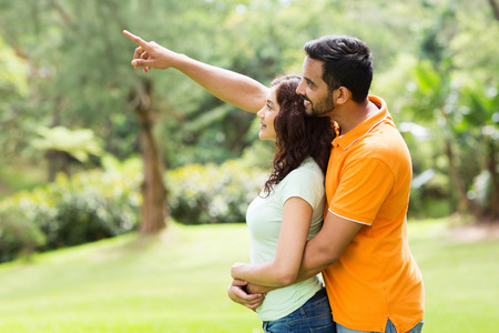 loving young indian couple looking and pointing in the forest