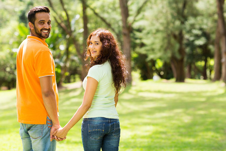 cute indian couple holding hands and looking back outdoors