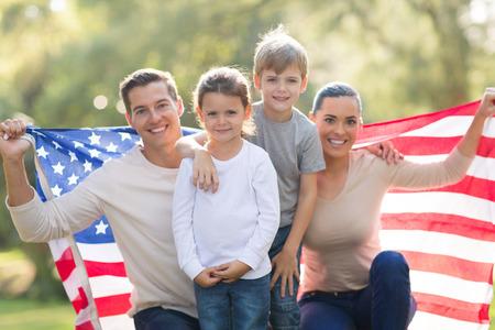 Photo pour portrait of beautiful modern american family with USA flag outdoors - image libre de droit