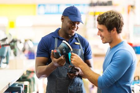 Photo pour friendly hardware store worker showing customer a sander - image libre de droit
