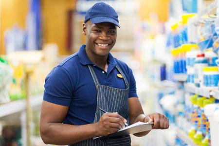 Photo pour happy african shop assistant checking stock in supermarket - image libre de droit
