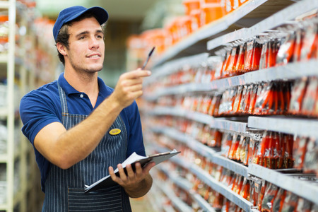 Photo for good looking hardware store worker counting stock - Royalty Free Image