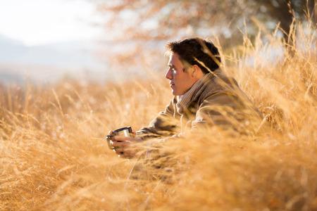 Foto de handsome man sitting in tall grass in autumn - Imagen libre de derechos