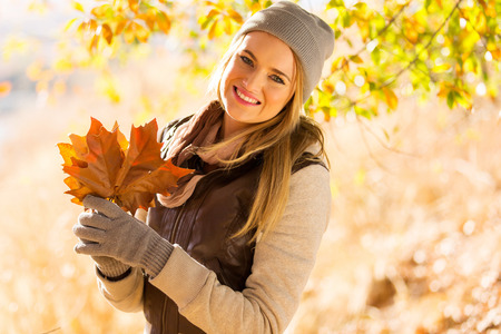 joyful young woman holding leaves in autumn park