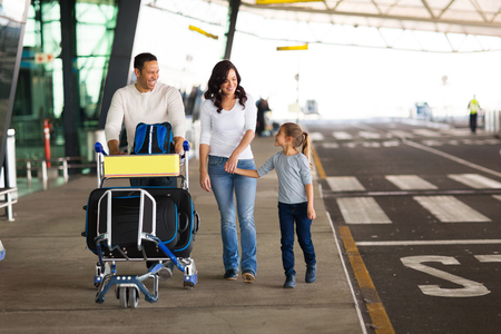 Photo pour cheerful young family at airport with a trolley full of luggage - image libre de droit