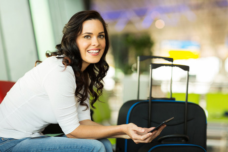 Photo pour smiling female traveller using tablet computer while waiting for her flight at airport - image libre de droit