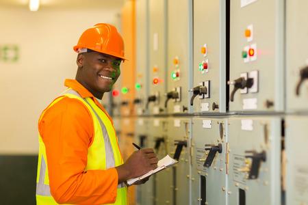 Photo pour happy young african industrial technician taking machine readings - image libre de droit