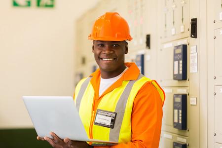 Photo pour portrait of african engineer holding laptop in power plant control room - image libre de droit
