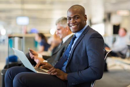 Foto de happy african business traveller with laptop computer at airport - Imagen libre de derechos