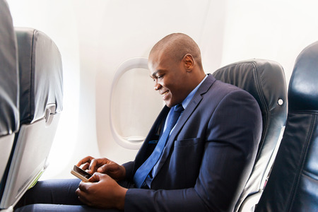 Foto de happy african airplane passenger using smart phone on plane - Imagen libre de derechos