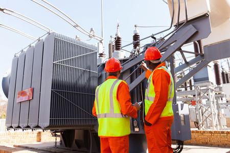 Foto de back view of electricians standing next to a transformer in electrical power plant - Imagen libre de derechos