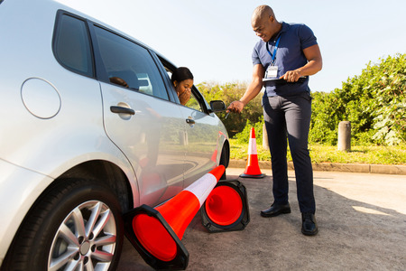 Photo for student driver making mistake during driving test, running over traffic cones - Royalty Free Image