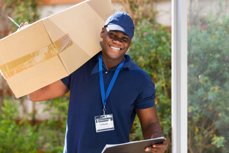 Photo pour cheerful african courier standing with parcel at the door - image libre de droit