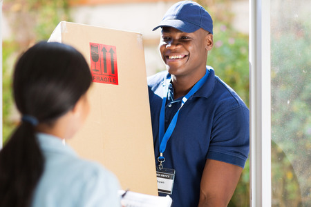 Foto de friendly young african american delivery man delivering a package - Imagen libre de derechos