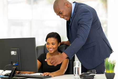 Photo pour friendly african boss guiding his new employee with her work - image libre de droit