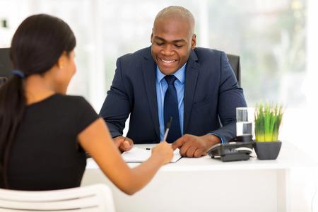 Foto de back view of african woman signing employment contract in office - Imagen libre de derechos