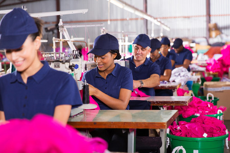 Photo pour group multiracial factory workers sewing in clothing factory - image libre de droit