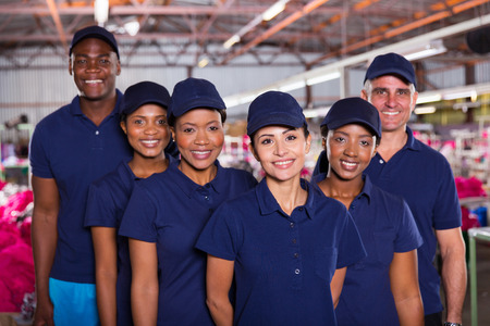 Photo pour group of happy clothing factory workers inside production area - image libre de droit
