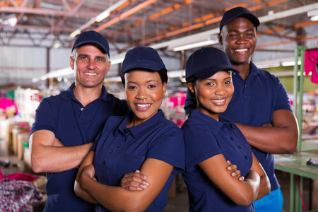 Photo pour happy textile factory co-workers with arms crossed - image libre de droit