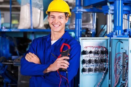 Foto de happy electrician holding digital insulation resistance tester - Imagen libre de derechos