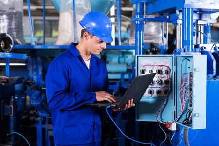 Foto de industrial programmer checking control box status with laptop computer - Imagen libre de derechos