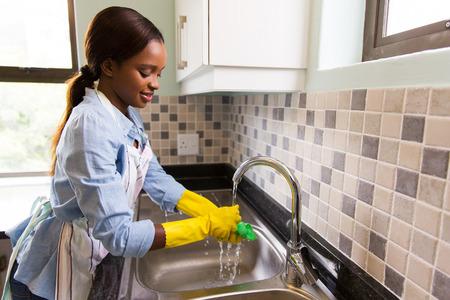Foto de beautiful african american woman doing house chores - Imagen libre de derechos