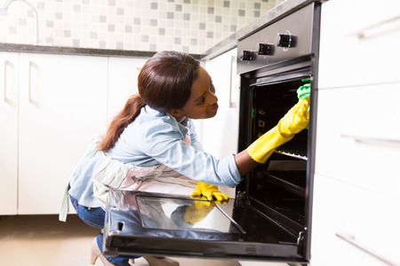 Photo pour african woman cleaning stove in the modern kitchen - image libre de droit