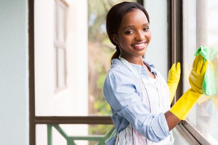 Foto de attractive african girl cleaning window glass - Imagen libre de derechos