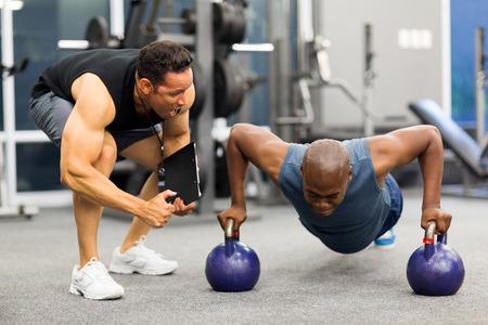 Foto de personal trainer motivates client doing push-ups in gym - Imagen libre de derechos