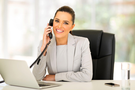 Foto de beautiful young businesswoman talking on landline phone - Imagen libre de derechos